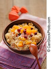 Millet porrige with pumpkin in clay bowl with wooden spoon