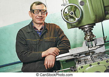 milling machine operator working in factory workshop