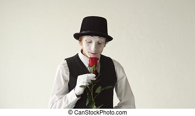 Mime artist holding a red rose on the white background