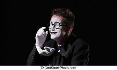 mime in a tuxedo with a bowtie cries and collects tears in...