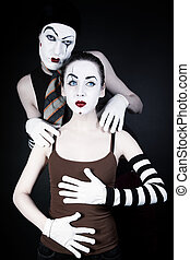 mime man tempts woman on a black background