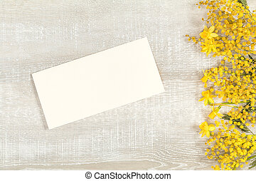 Mimosa and yellow daffodils on a light wooden surface -...