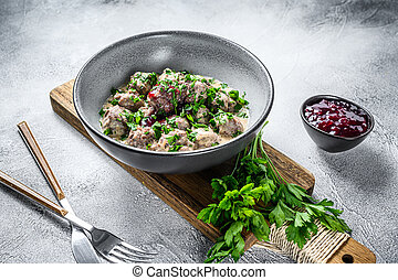 Mince meat meatballs with cream sauce on a plate. White wooden background. Top view