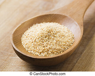 Minced garlic on a wooden spoon