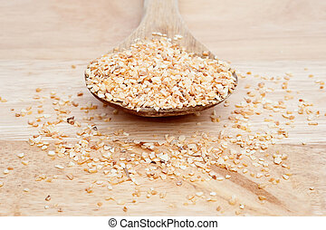 Minced Garlic on wooden serving spoon with selective focus -...
