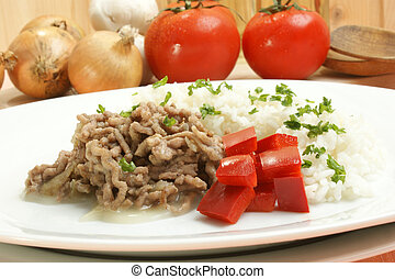 Minced meat with rice and paprika on a white plate