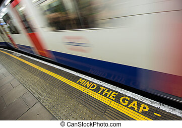Mind the gap sign with speeding train in London underground