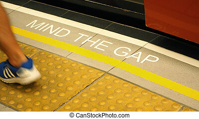 Mind the gap text sign on floor.