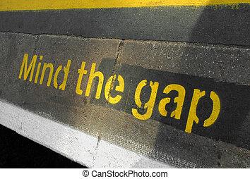 mind the gap warning sign on a railway or subway platform