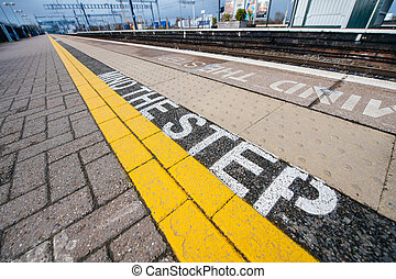 Mind the step yellow text line in British train station