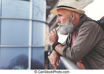 Mindful bearded elder man smoking