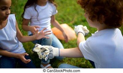 Mindful boy handing over gloves for voluntary female mates -...