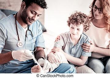 Mindful doctor bandaging foot of teen patient