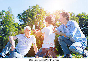 Mindful father teaching son how to take photos