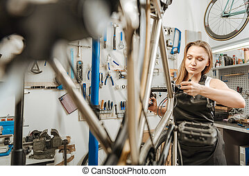 Mindful mechanic renovating the bicycle in the repair shop