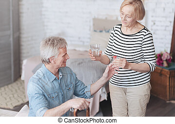 Mindful senior wife taking care of her loving husband