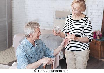 Mindful senior wife taking care of her loving husband