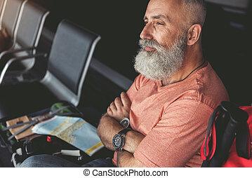 Mindful smiling elder man in waiting hall