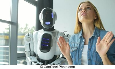 Mindful young lady showing robot its workplace - First...
