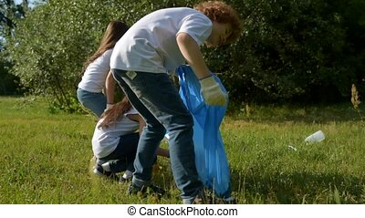Mindful young volunteers cleaning local park area -...