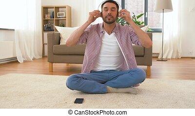 man in headphones meditating in lotus pose at home -...