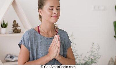 woman meditating in lotus pose at yoga studio - mindfulness,...