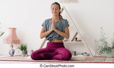 woman meditating in lotus pose at yoga studio - mindfulness,...