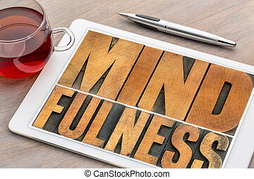 mindfulness word in wood type on tablet