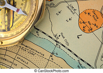 An old surveying compass on an out-of-copyright geological ressearch map, showing different rock strata and palaeontological zpnes, fault lines and dipped bedding planes, symbolising mineral exploration or geological mapping.
