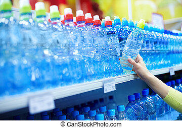 Mineral water - Close-up of female choosing good mineral ...