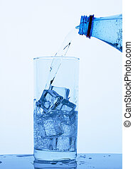 Mineral water from the bottle is poured into the glass with ice