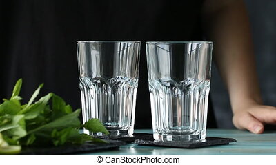 Mineral water in the glass with ice cubes, mint, lime and lemon slices