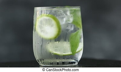 Mineral water in the glass with ice cubes,mint, lime and lemon slices on black background