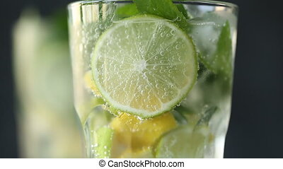 Mineral water in the glass with ice cubes,mint, lime and lemon slices