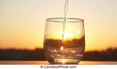 Mineral water is being poured on the sunset background. Slow...