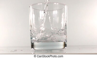 mineral water is poured into a glass slow motion.