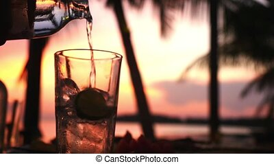 Mineral water is pouring in glass with ice on the sunset background in a beach cafe. slow motion.