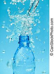 Mineral water - splash water from bottle on blue