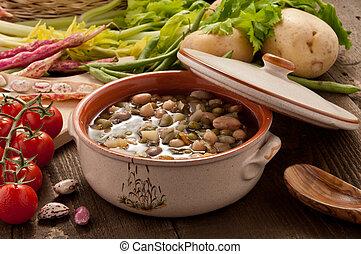 Minestrone di verdure ambientata con ortaggi su piano di legno