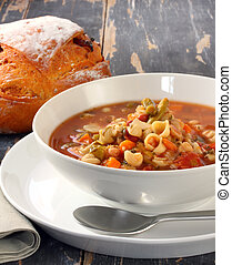 Minestrone pasta soup on rustic table, with fresh-baked cob of bread.