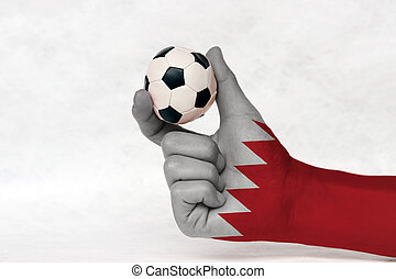 Mini ball of football in Bahrain flag painted hand, hold it with two finger on white background. Concept of sport or the game in handle or minor matter.