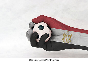 Mini ball of football in Egypt flag painted hand on white background. Concept of sport or the game in handle or minor matter. red white black color with the Egyptian eagle of Saladin.
