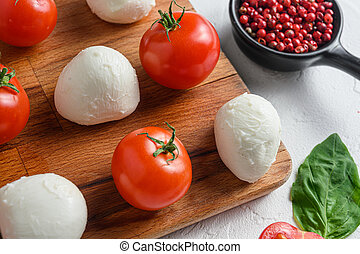 Mini balls of mozzarella cheese, on chop wood board ingredients for salad Caprese. over white background. close up selective focus