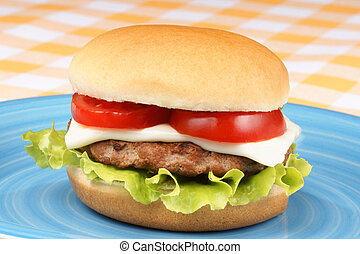 Mini cheese burger with tomato and lettuce on a blue dish