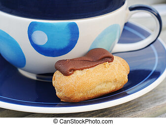 Mini chocolate choux pastry with blue decorated cup and saucer