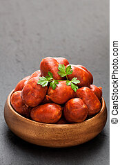 Mini chorizo sausages in wooden bowl on black stone background