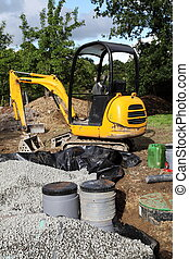 A mini digger being used to install a sand and gravel filter for a domestic septic tank and sewage system