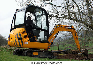 Mini Digger - Man in a mini digger digging a trench in a...