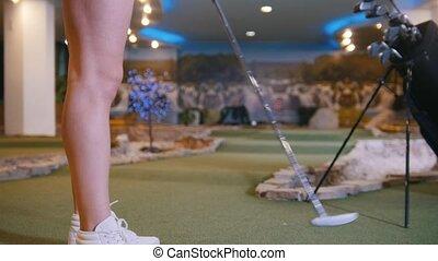 mini, femme, golf, golf., jeune, frapper, balle, indoors., jouer