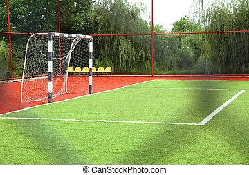 Mini Football Goal On An Artificial Grass . football goal on a green lawn . football field near fence at day sunny day